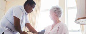 nurse checking senior's blood pressure